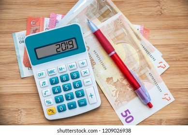 2019 written on a calculator and euros banknotes on wooden background