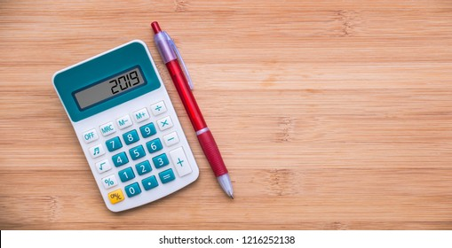 2019 written on a calculator and a pen on wooden background