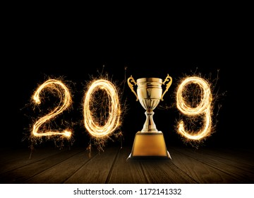 2019 written with Sparkle firework with champion golden trophy on black background.