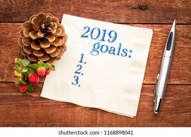 2019 year goals list on a napkin on a wood table with  season decoaration