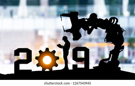 2019 years of robot assistant technology , industry 4.0 , artificial intelligence trend concept. Silhouette of business man control automation robo advisor arm in blur smart building bakckground.