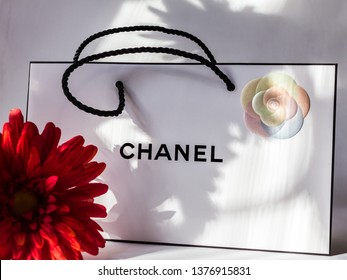 2019.03.07, Moscow, Russia. White bag of Chanel on the white background and red flower.