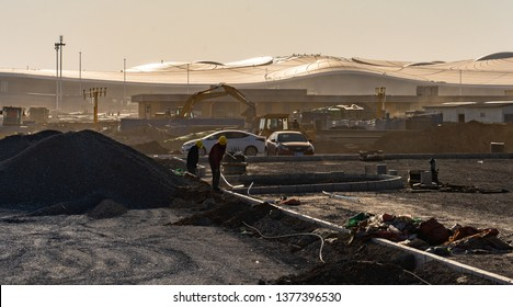 2019.04.22 Beijing, China  Beijing Daxing international airport construction site in the remote, two workers are cleaning up the site. The airport terminal looks like an alien spaceship from far
