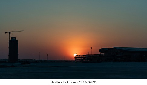2019.04.22 Beijing, China  Beijing Daxing international airport construction site . 6pm sunset, shines golden color on the terminal.  A flight fly over just in time.