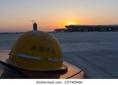 2019.04.22 Beijing, China  Beijing Daxing international airport construction site . 6pm sunset, shines golden color on the terminal. A hat in close up. Caption: China west construction