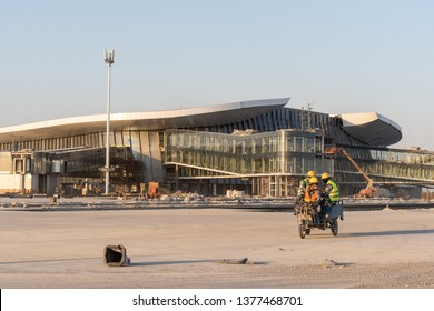 2019.04.22 Beijing, China  Beijing Daxing international airport construction site in the remote. Workers commute with tricycle wearing a mask.Sunset