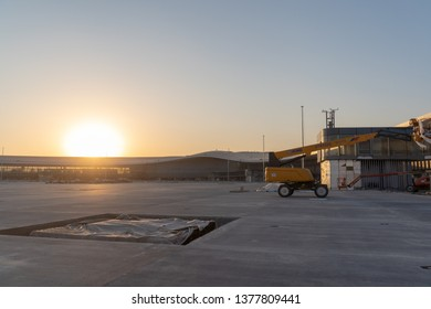 2019.04.22 Beijing, China  Beijing Daxing international airport construction site . 6pm sunset, shines golden color on the terminal, a construction machine parked on the runway