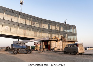 2019.04.22 Beijing, China  Beijing Daxing international airport construction site . 6pm sunset, shines golden color on the terminal, workers worked on the interral
