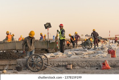 2019.04.22 Beijing, China  Beijing Daxing international airport construction site. Workers working on the runway. 6pm, Sunset shines golden color on everything