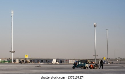2019.04.22 Beijing, China  Beijing Daxing international airport construction site. The sign on the runway, lights was installed on the light pole. Two workers are reparing the ground