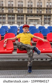 2019.05.10, Tula, Russia. A boy wearing yellow polo, baseball hat and  camouflage pants sits on the red stadium seats.
