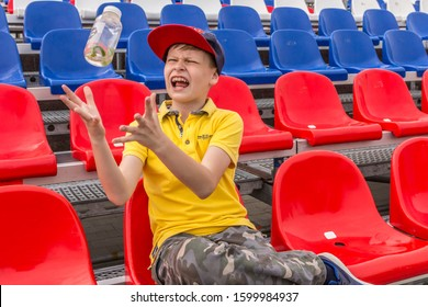 2019.05.10, Tula, Russia. A boy wearing yellow polo, baseball hat and  camouflage pants sits on the red stadium seats. A boy having fun.