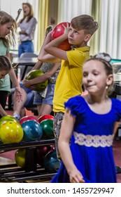 2019.05.22, Maloyaroslavets, Russia. A boy holding bowling ball and going to throw it. Children having fun.