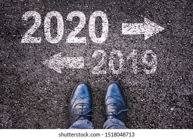 2020 and 2019 with direction arrows written on an asphalt road background with legs