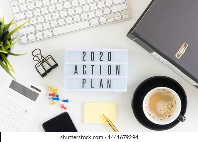 2020 action plan lightbox on office table with keyboard, coffee, calculator, stationery, box file and smartphone.