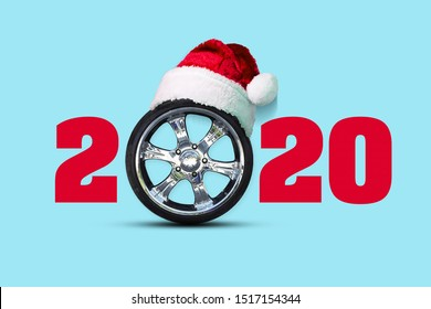 2020. Auto wheel instead of zero. Santa hat. Isolated on blue background. New Year background. Greeting card for a car workshop. Auto mechanics.