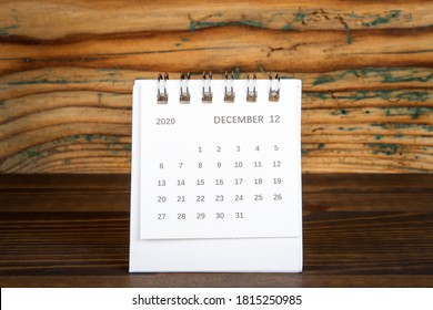 2020 DECEMBER. White paper calendar on a wooden table. Time planning, day counting and holidays