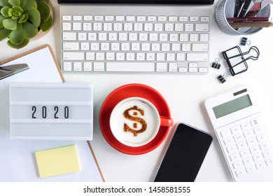 2020 financial planning and investment concepts. View of coffee cup with dollar sign latte art, computer, stationery and smartphone on office table.