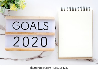 2020 goals on wood box and blank notebook paper on white marble background, 2020 business new year aim to success