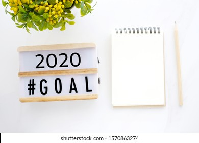 2020 goals on wood box and blank notebook paper on white marble background, business new year aim to success