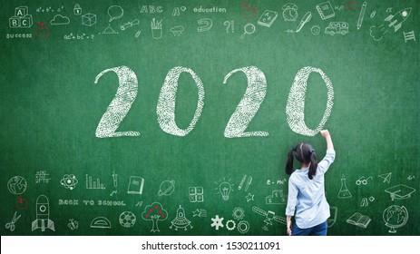 2020 Happy new year school class academic calendar with student kid's hand drawing greeting on teacher's green chalkboard for educational celebration, back to school, STEM education classroom schedule