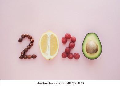 2020 aus gesundem Essen auf rosafarbenem Hintergrund, Happy New Year, Gesundheit Ernährung Auflösung, Ziele und Lifestyle