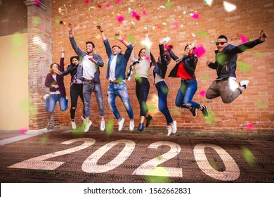 2020 New Year celebration written on floor. Group of friends jumping together on the symbol of new year to have lucky in front of a brick wall