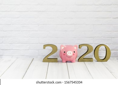 2020 new year and  piggy bank on white wood table over white background with copy space , saving concept