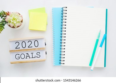 2020 on wood box, blank notebook paper on white marble table background, 2020 new year mock up, template with copy space for text, top view