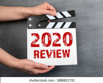 2020 Review. Business concept. Movie clapper in woman hand. Black chalk board background.