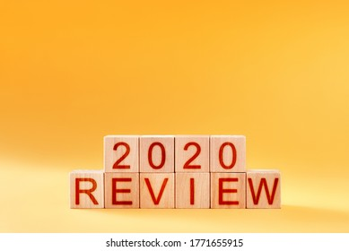 2020 review. wooden blocks with an inscription on a yellow background