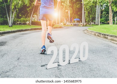 2020 symbolism of the beginning of the new year. A beautiful girl running on the road. The goal of success.