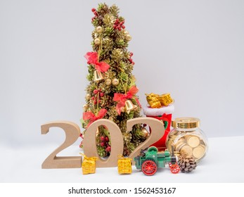 2020 wooden character, Christmas tree and glass piggy bank with decoration on white background, Have a nice holiday on this Christmas and new year.