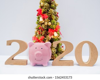 2020 wooden character, Christmas tree and pink piggy bank with decoration on white background, Have a nice holiday on this Christmas and New Year.