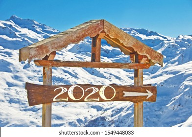 2020 written on a wooden direction sign, snow mountain landscape on the background, ski resort holiday greeting card