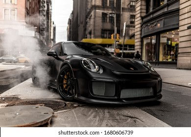 2020.02.25 New York, New York Two Porsches in Manhattan by a manhole opening with smoke rising