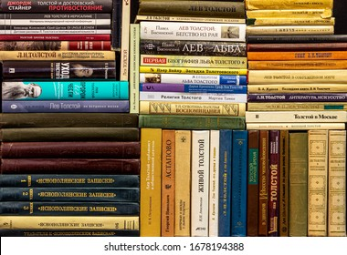 2020.03.17, Moscow, Russia. piles and rows of colorful covers of books by Leo Tolstoy and about Tolstoy on a black background.