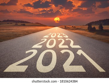 2021 2022 and 2023 new year written on highway as future and success concept against the happy looking sunset.