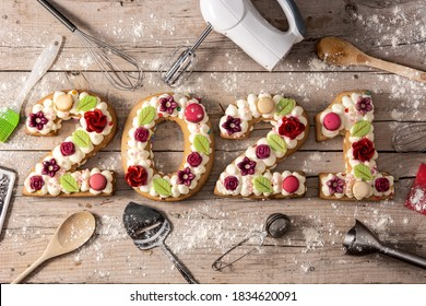 2021 cake decorated with flowers on wooden background.