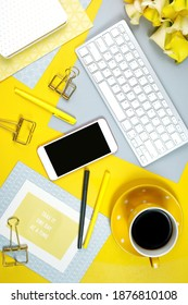 2021 colors of the year, yellow and gray, desktop workspace with keyboard, smart phone and desk accessories. Top view blog hero header creative composition flat lay.