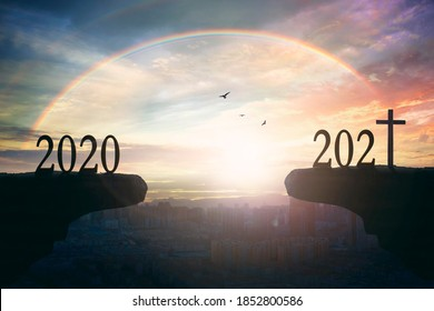 2021 concept: Silhouette of year 2021 and cross  on mountain  with city sunset  background