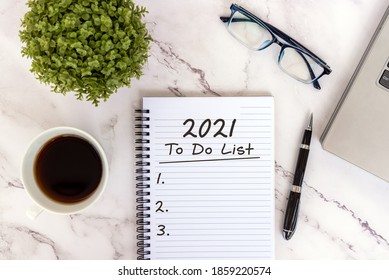 2021 To do list text on note pad with smart phone, laptop, coffee, eyeglasses and pen.