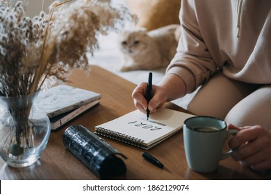 2021 goals, new year resolution, planning. Woman writing in Notebook with text 2021 loading on the table in apartments with cat. Selective focus