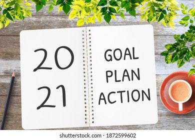 2021 Goals and New Year`s resolutions with Christmas decorations. Overhead view. with cup of coffee and glasses.Planning concept for New Year and Christmas.
