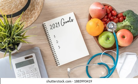 2021 goals on note book for new year list reminder in notebook of yearly planner and health plan for work-life balance on desk background of computer, healthy food, face mask for covid-19 protection