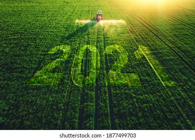 2021 Frohes Neujahrskonzept und Luftbild des Pflügens und Sprühens von Traktoren auf dem Feld.