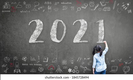 2021 Happy new year school class academic calendar with student kid's hand drawing greeting on teacher's black chalkboard for educational celebration, back to school, STEM education classroom schedule