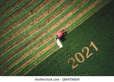 2021 Happy Ney Wear concept and red tractor mowing green field.