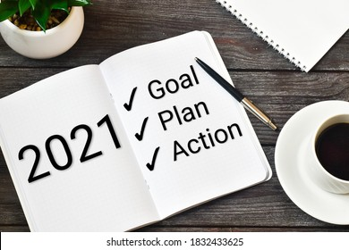 2021 New Year. Goal,plan, action text on notepad with office accessories on a wooden background. Business motivation, inspection concepts ideas. - Shutterstock ID 1832433625