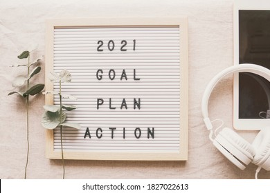 2021 New year resolution, Goal, Plan and action on letter board with tablet and headphone